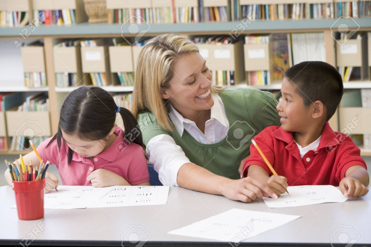Two students in class writing with teacher helping Stock Photo - 3207654