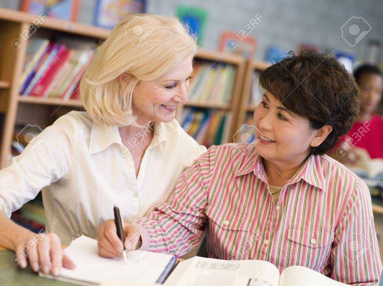 Two women sitting in library with a book and notepad (selective focus) Stock Photo - 3194541