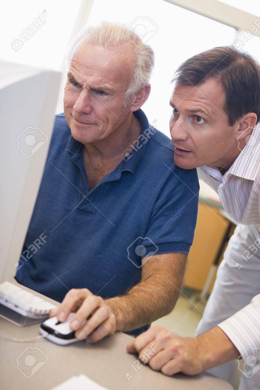 Two men at computer looking at monitor (high key) Stock Photo - 3194611
