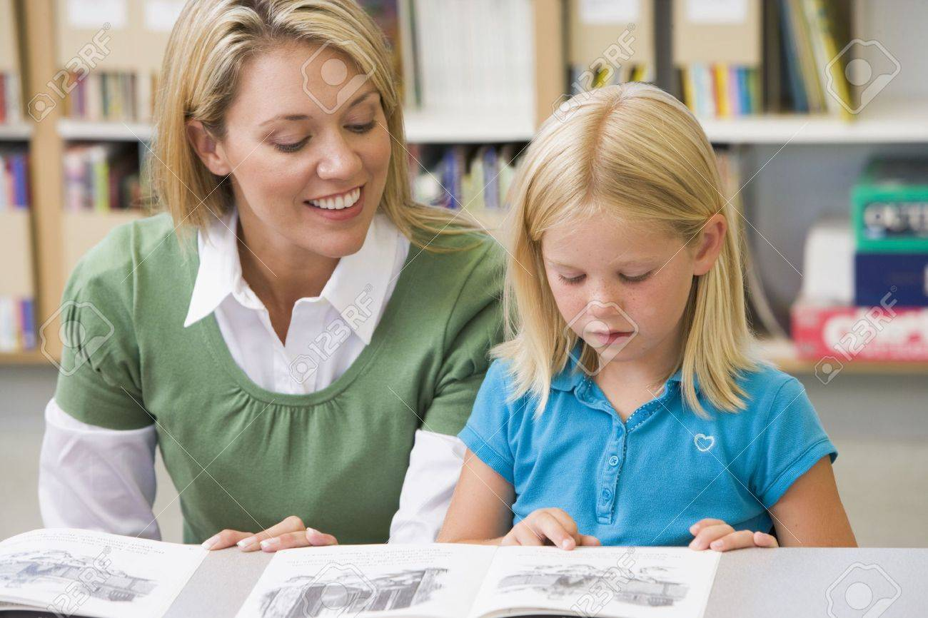 Student in class reading with teacher Stock Photo - 3207550