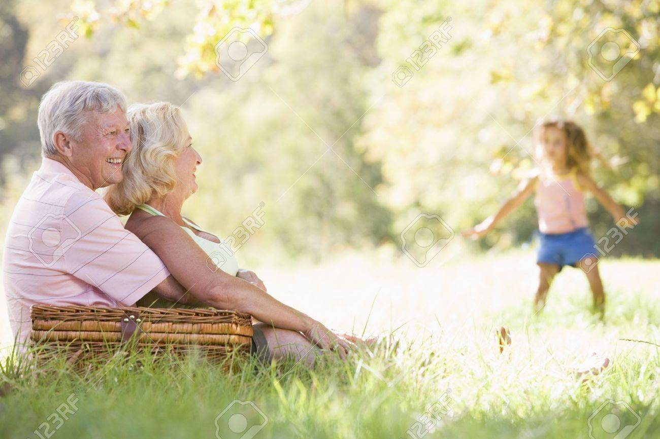 Grandparents at a picnic with young girl in background dancing Stock Photo - 3460084