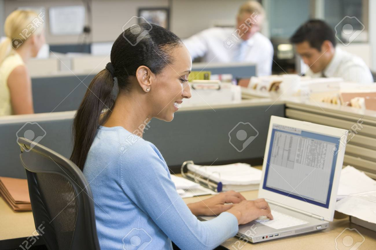 Businesswoman in cubicle using laptop smiling Stock Photo - 3471660