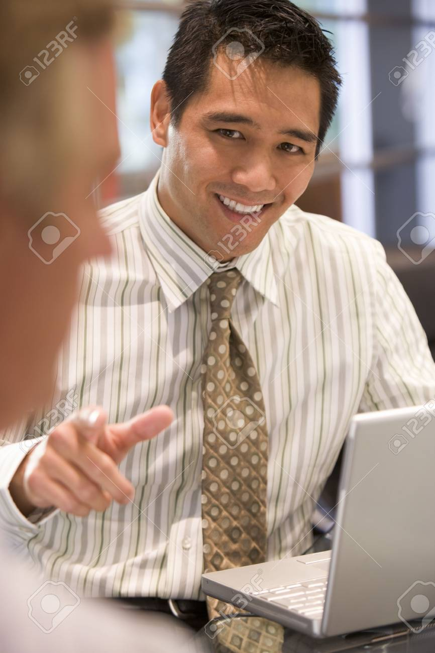 Two businessmen in boardroom with laptop talking Stock Photo - 3458889