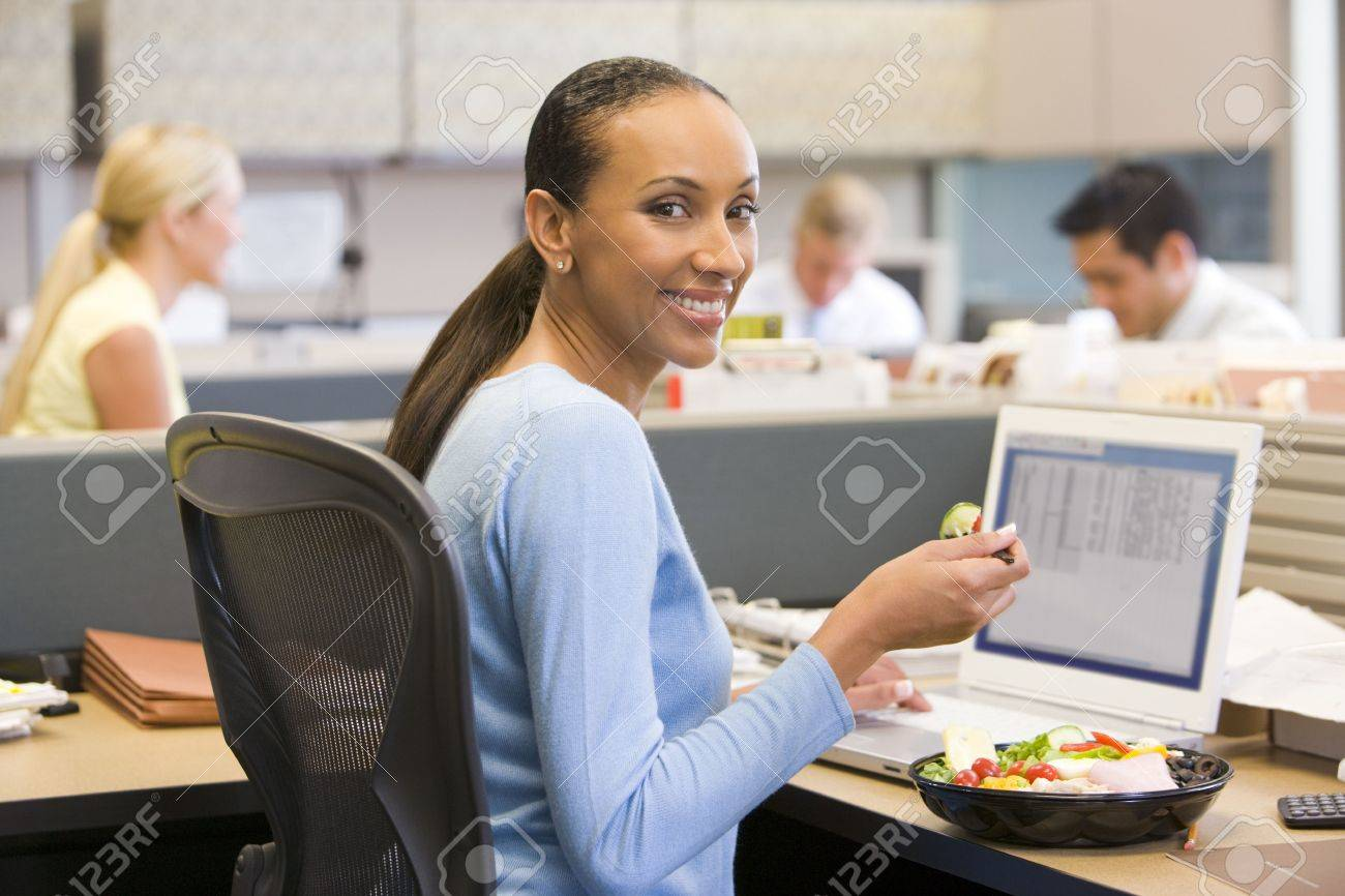Businesswoman in cubicle with laptop eating salad Stock Photo - 3471076