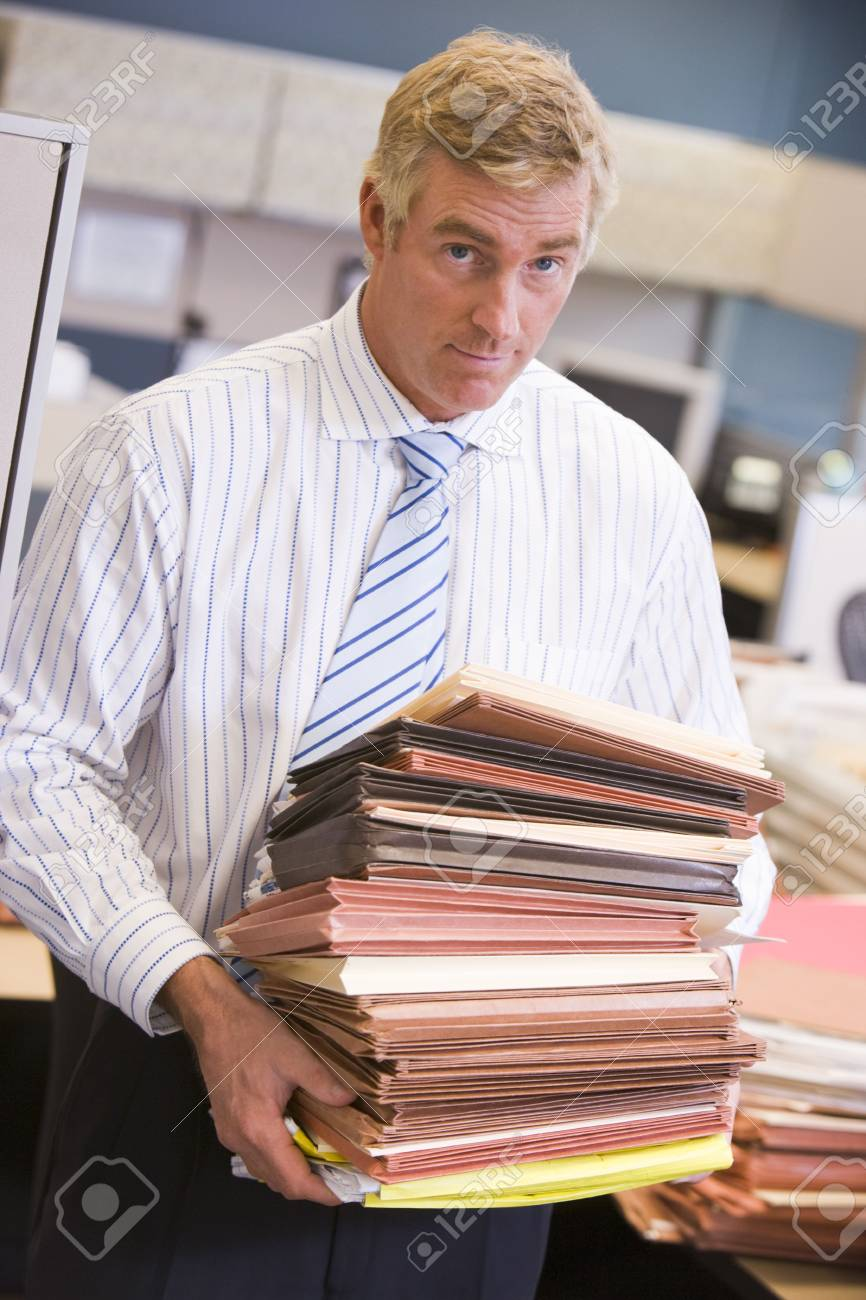 Businessman standing in cubicle with stacks of files Stock Photo - 3474930