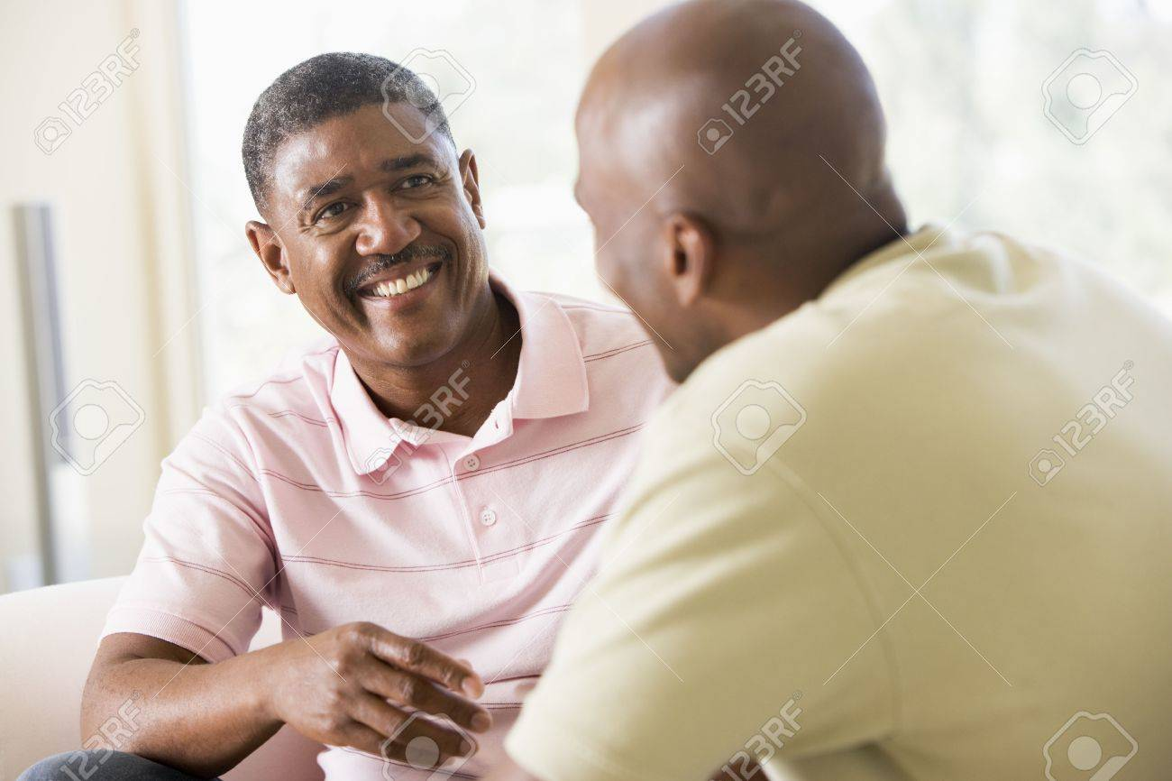 Two men in living room talking and smiling Stock Photo - 3458906