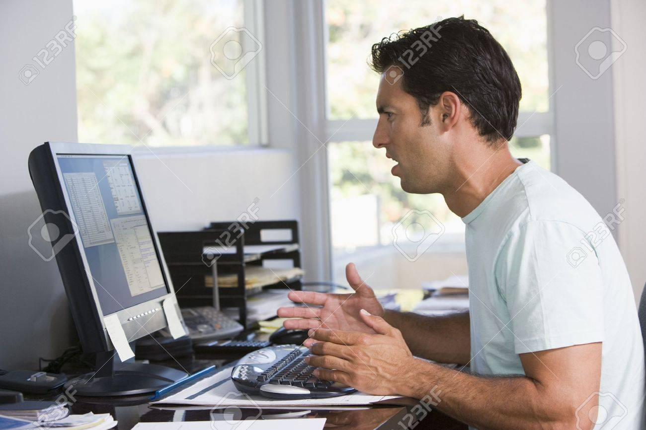 Man in home office using computer looking frustrated Stock Photo - 3460877
