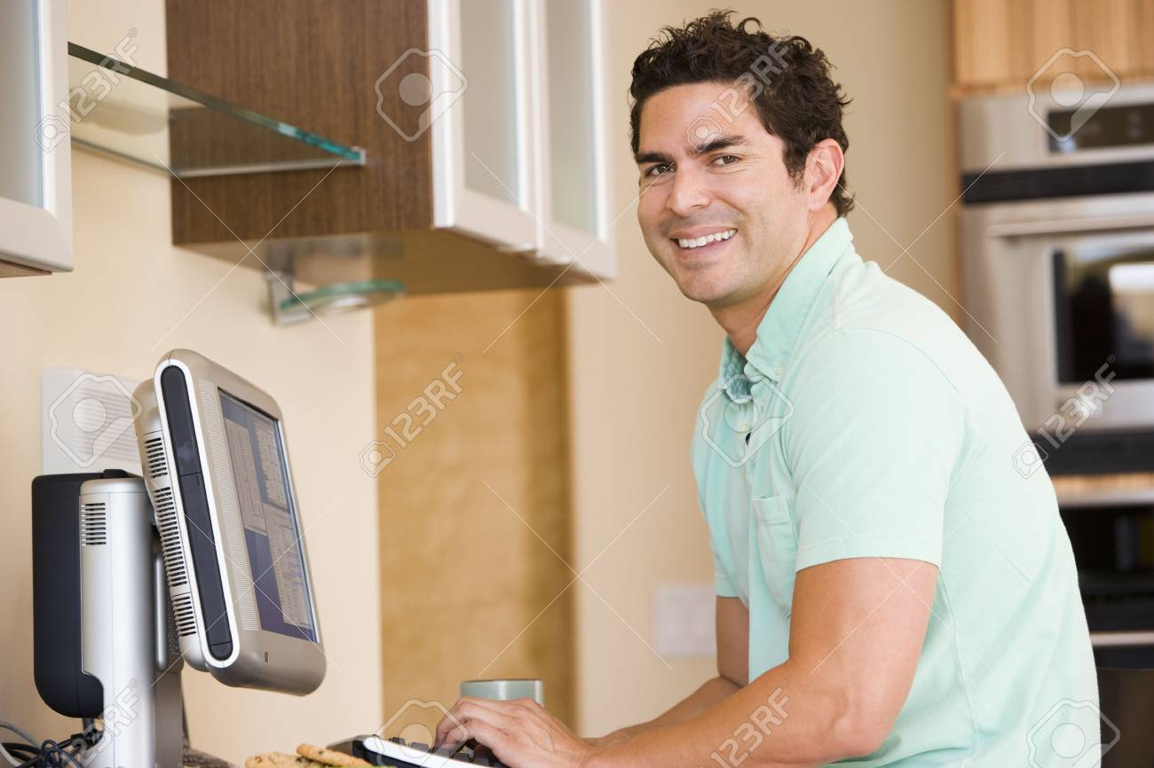 Man in kitchen using computer and smiling Stock Photo - 3461229
