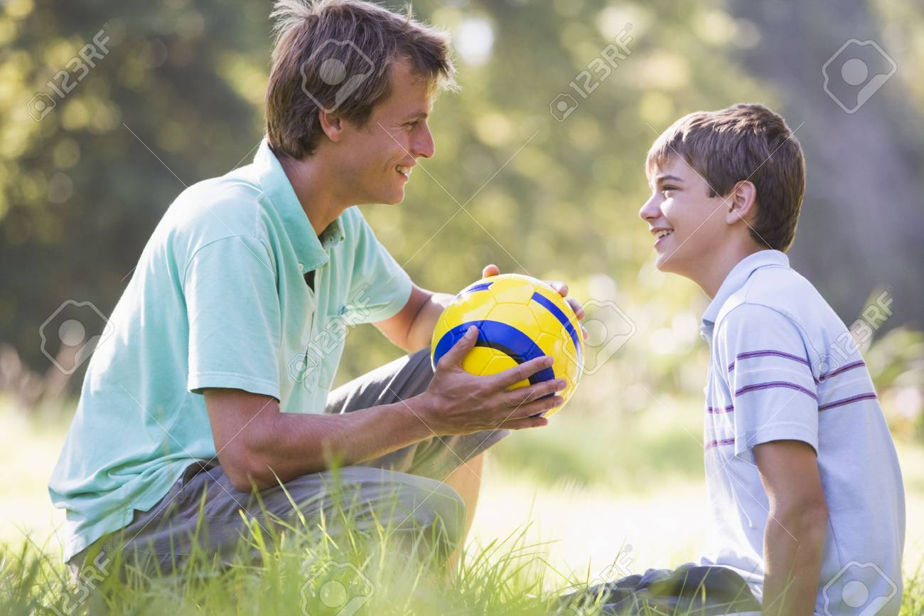 Man and young boy outdoors with soccer ball smiling Stock Photo - 3475031