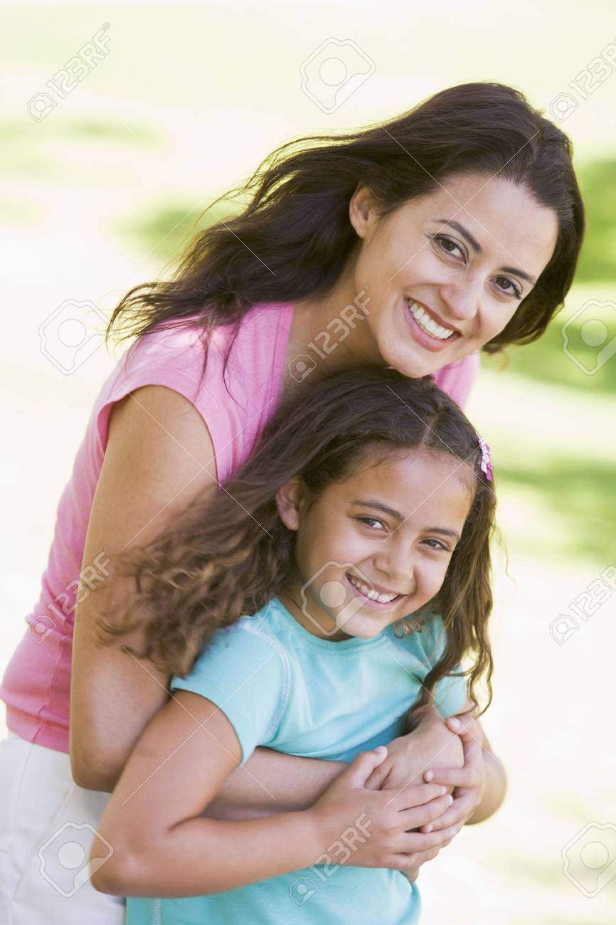 Woman and young girl outdoors embracing and smiling Stock Photo - 3460913
