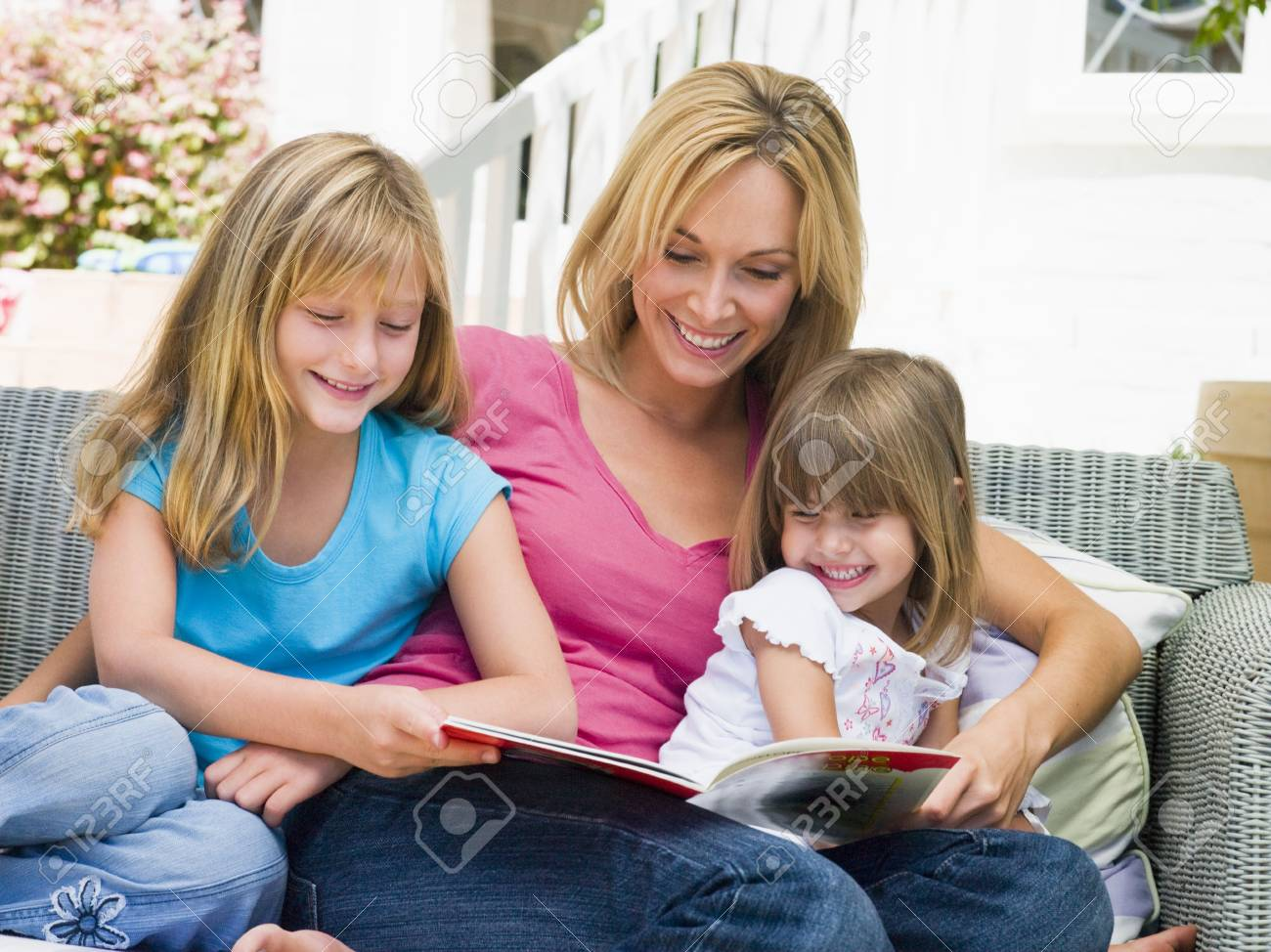 Woman and two young girls sitting on patio reading book smiling Stock Photo - 3475551
