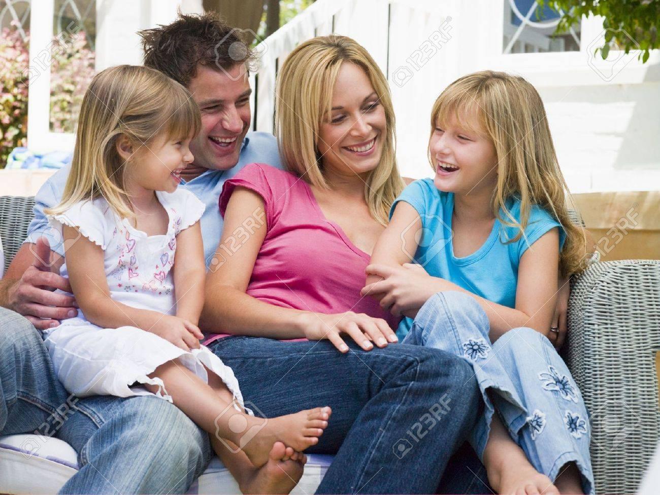 Family sitting on patio smiling Stock Photo - 3475579