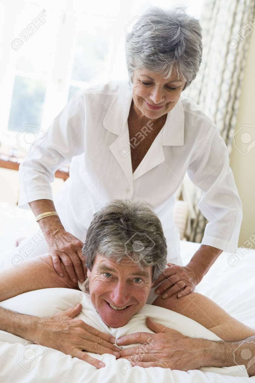 Woman giving man massage in bedroom smiling Stock Photo - 3461120