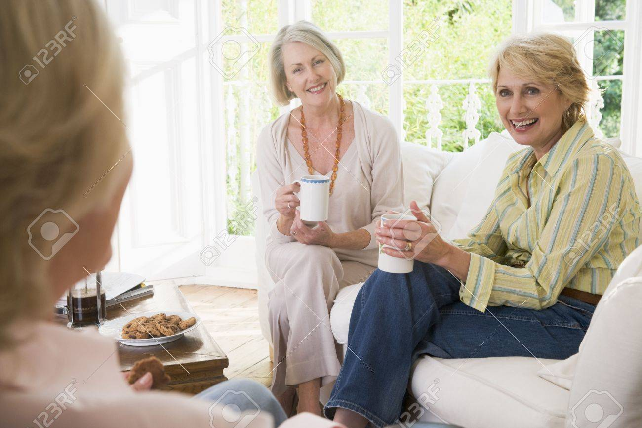 Three women in living room with coffee smiling - 3475833
