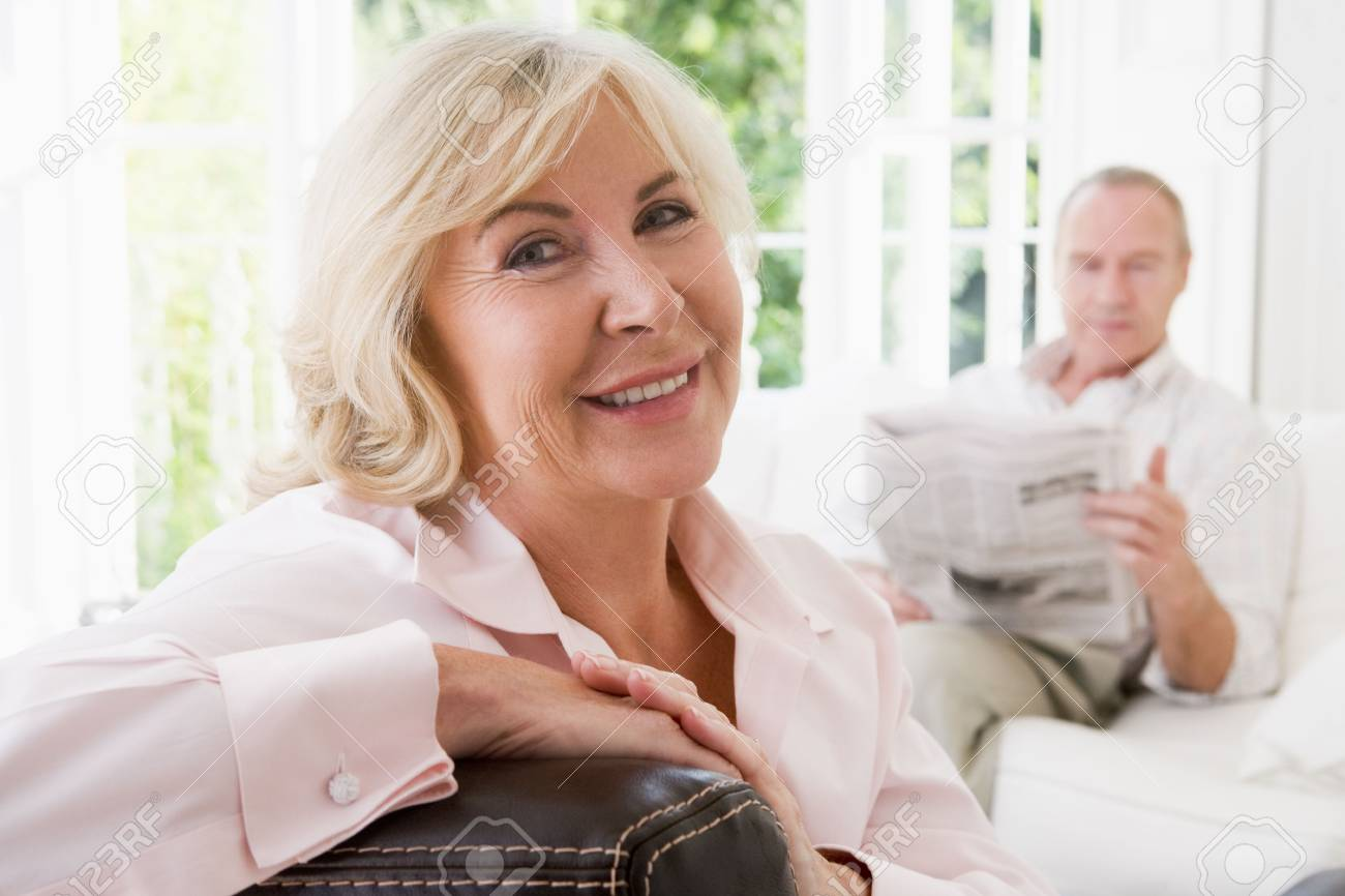 Woman in living room smiling with man in background reading newspaper Stock Photo - 3475632