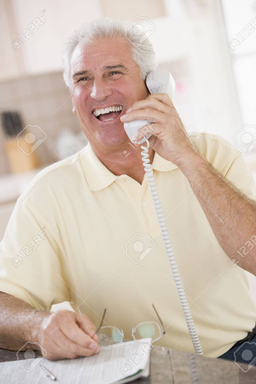 Man in kitchen on telephone laughing Stock Photo - 3475647