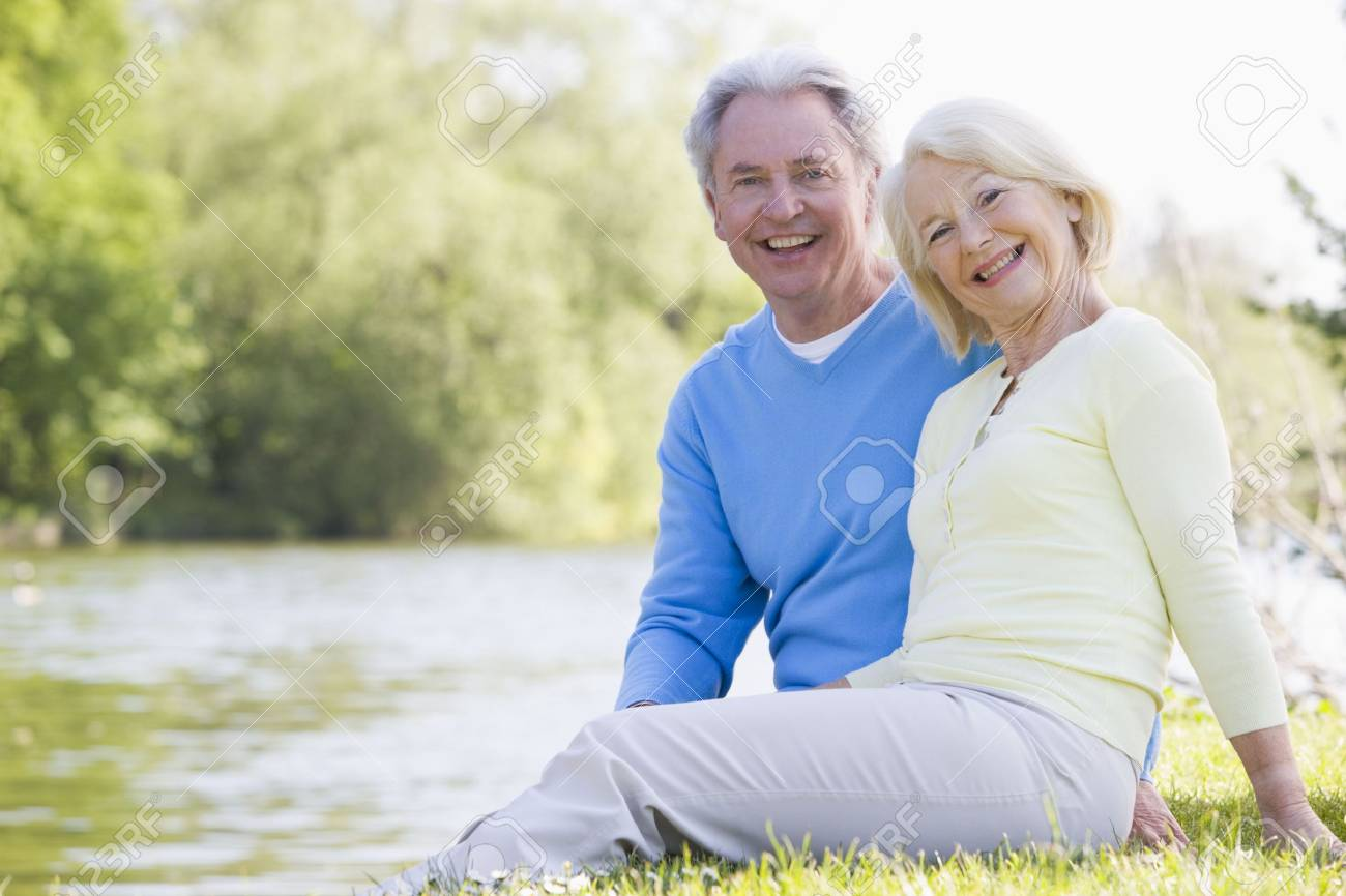 Couple outdoors at park by lake smiling Stock Photo - 3475589