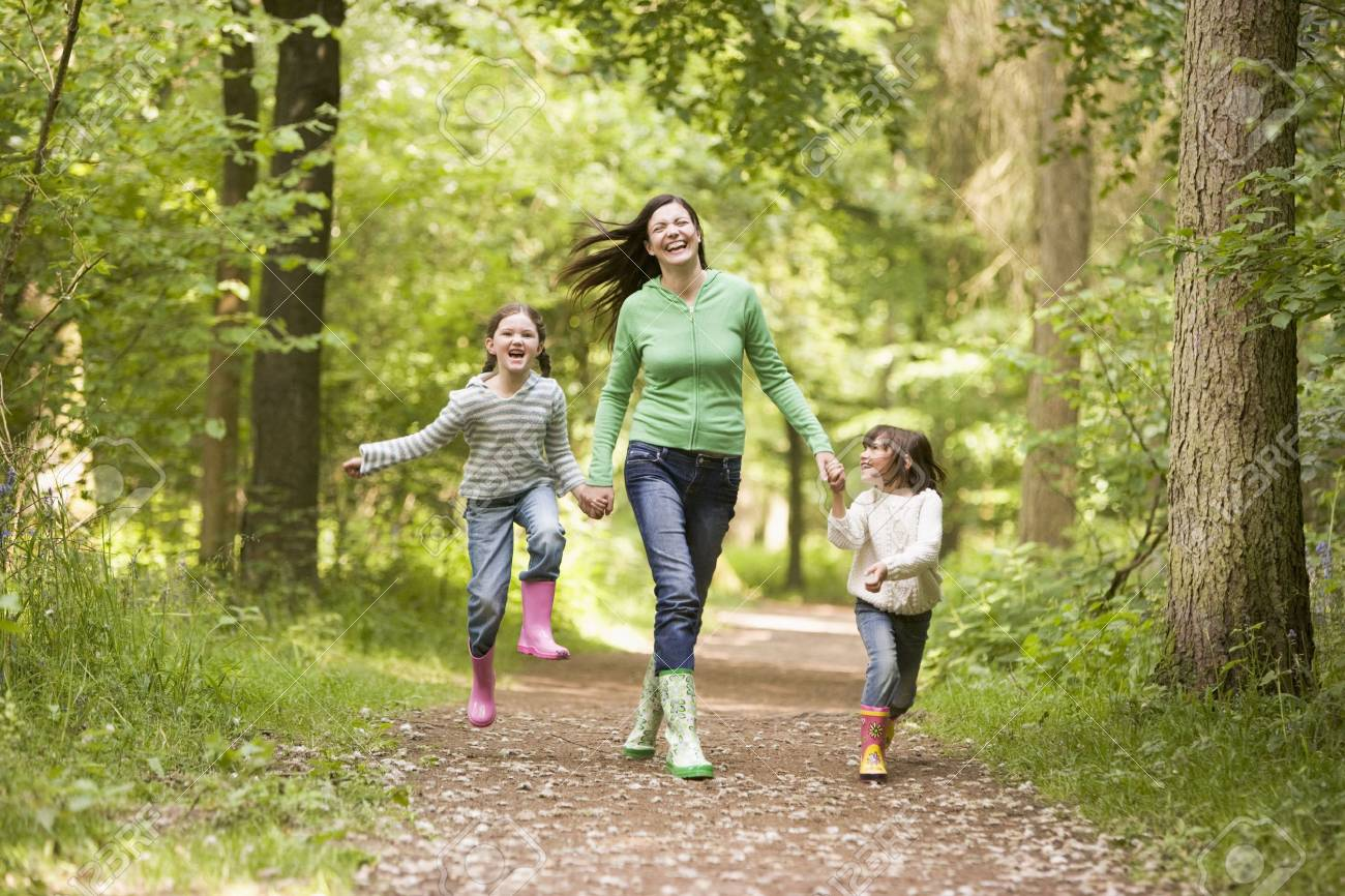 Mother and daughters skipping on path smiling Stock Photo - 3476336