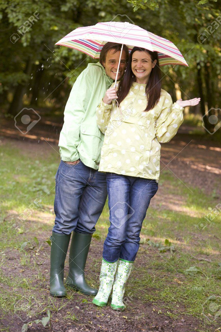 Couple outdoors in rain with umbrella smiling Stock Photo - 3477275