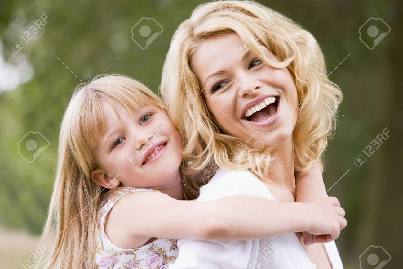 Mother holding daughter outdoors smiling Stock Photo - 3600186