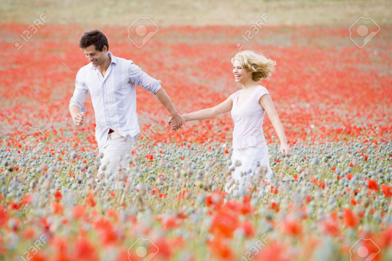 Couple walking in poppy field holding hands smiling - 3600150
