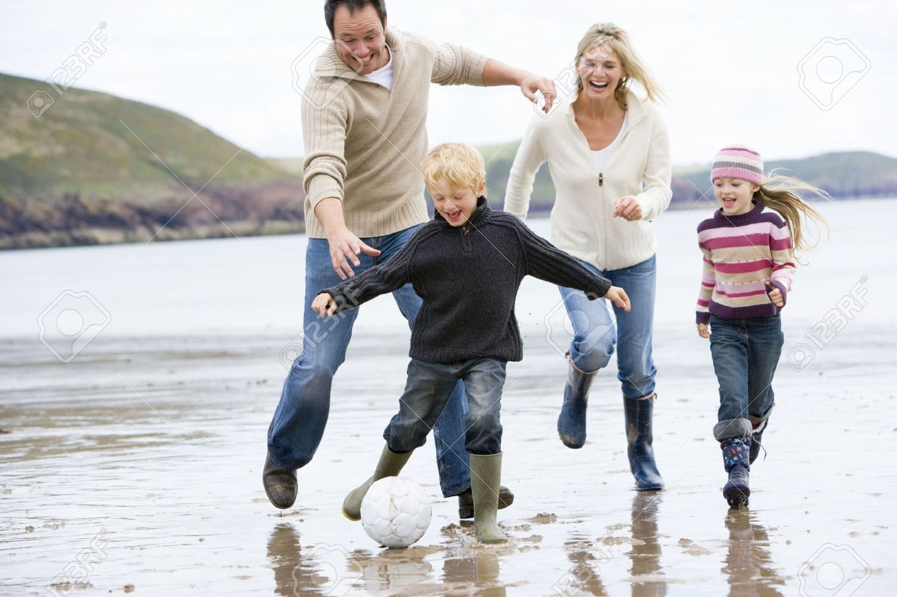 Family playing soccer at beach smiling Stock Photo - 3600126