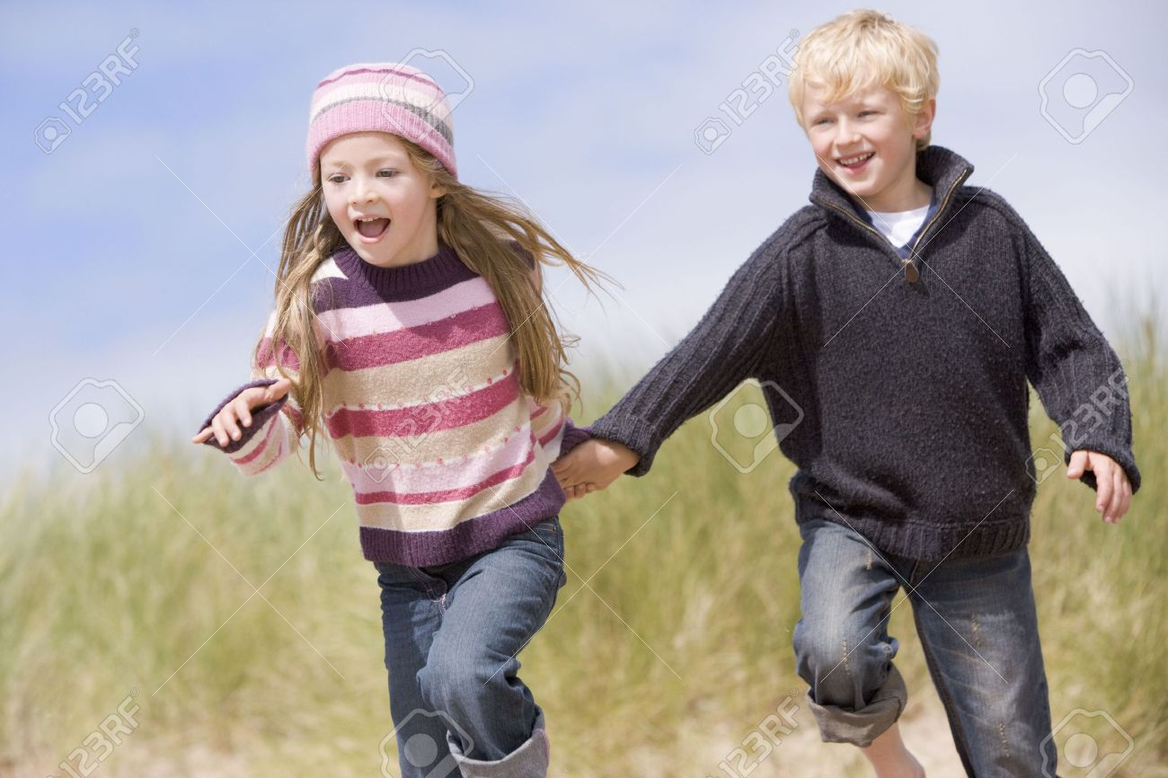 Two young children running on beach holding hands smiling Stock Photo - 3600184