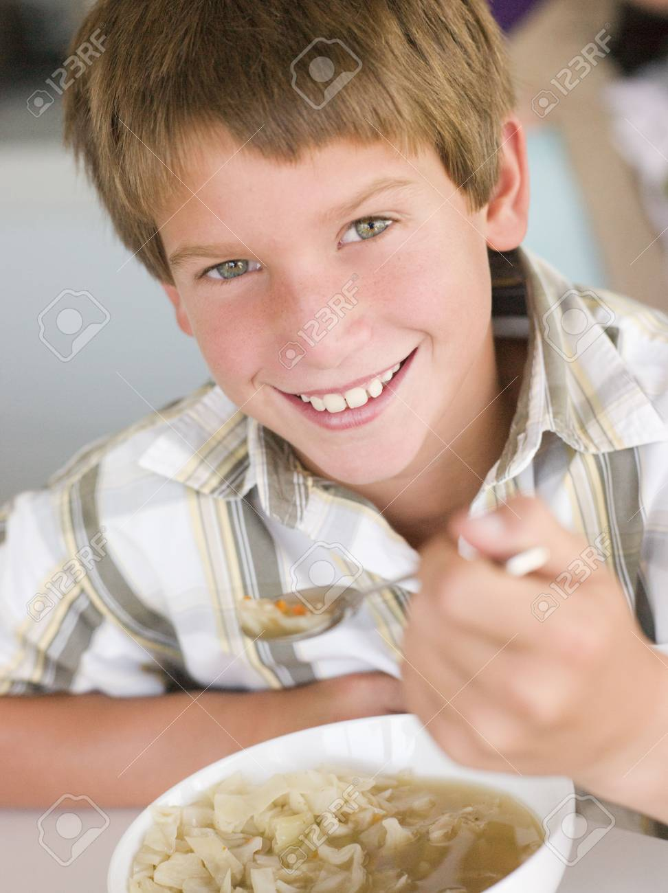 Young boy in kitchen eating soup and smiling Stock Photo - 3507212