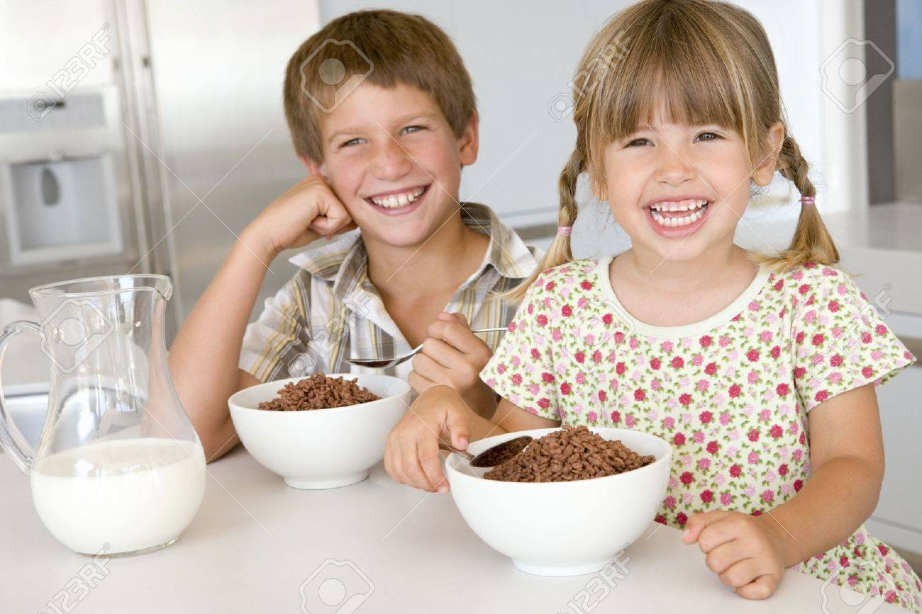 Two young children in kitchen eating cereal smiling Stock Photo - 3507093