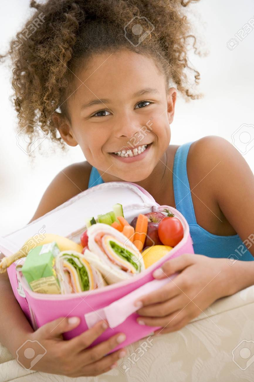 Young girl holding packed lunch in living room smiling Stock Photo - 3507140
