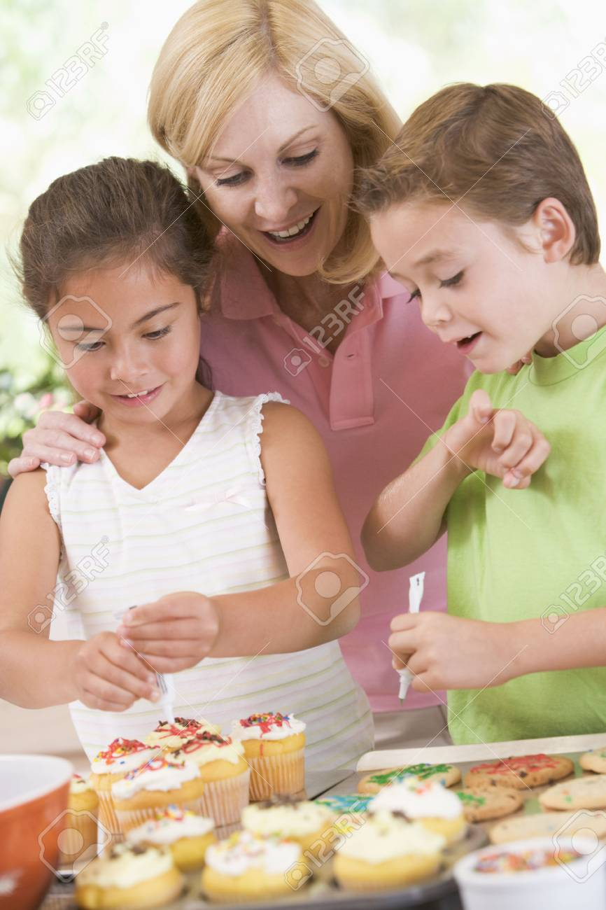 Woman with two children in kitchen decorating cookies smiling Stock Photo - 3507007