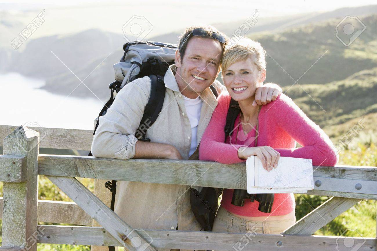 Couple on cliffside outdoors leaning on railing and smiling Standard-Bild - 3603691