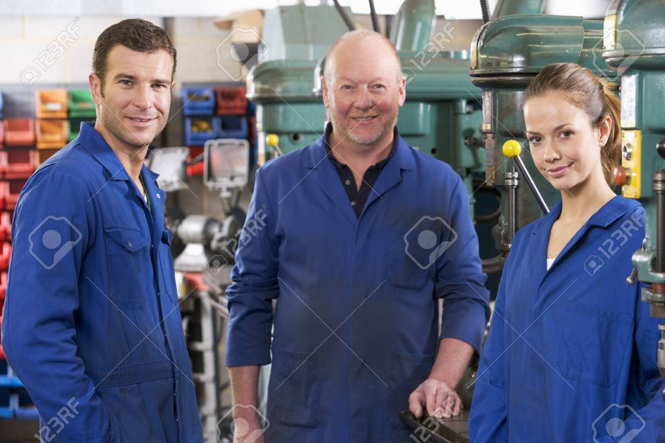 Three machinists in workspace by machine talking Stock Photo - 3603439
