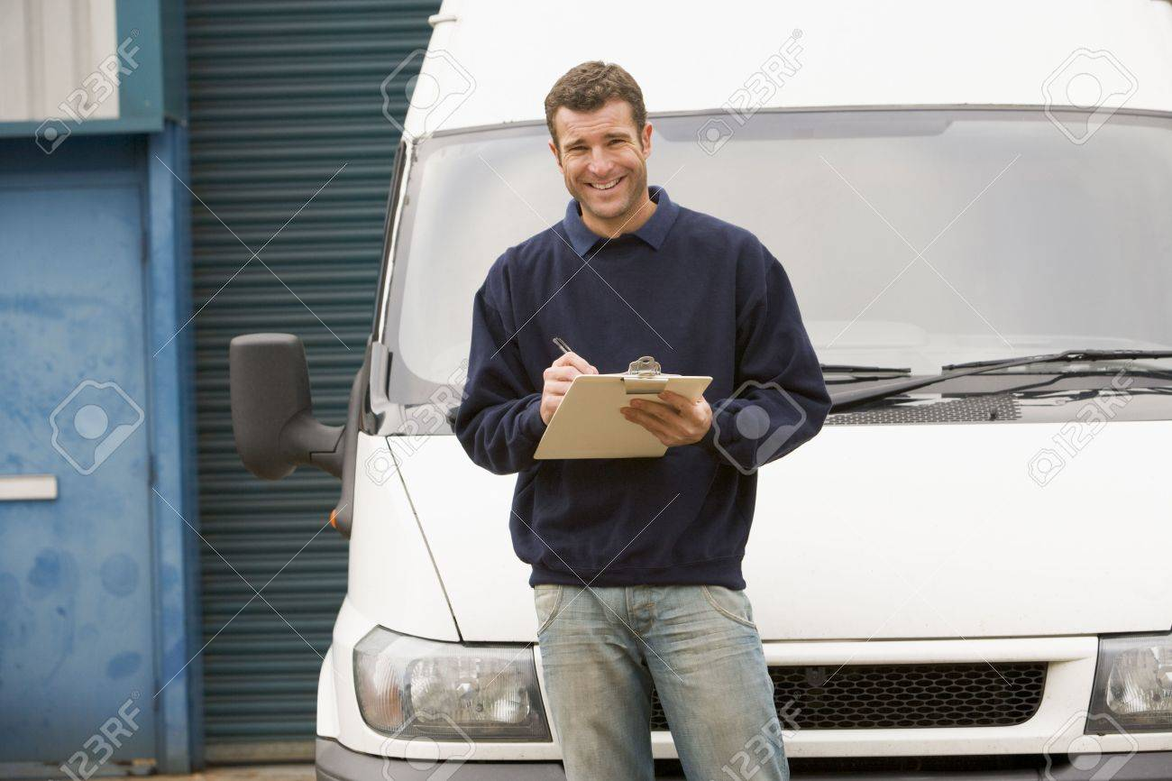 Deliveryperson standing with van writing in clipboard smiling - 3601387