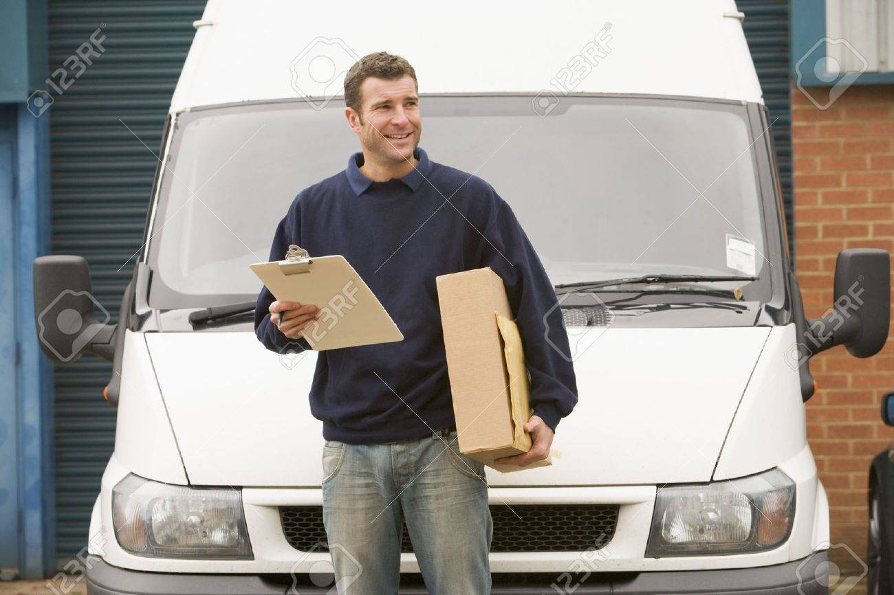 Deliveryperson standing with van holding clipboard and box smiling - 3601394