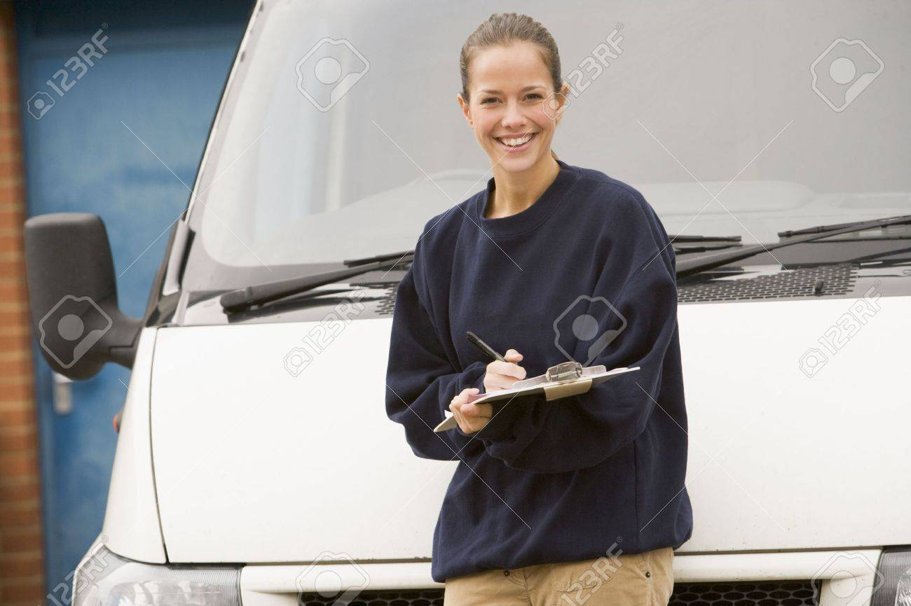 Deliveryperson standing with van writing in clipboard smiling Stock Photo - 3601032