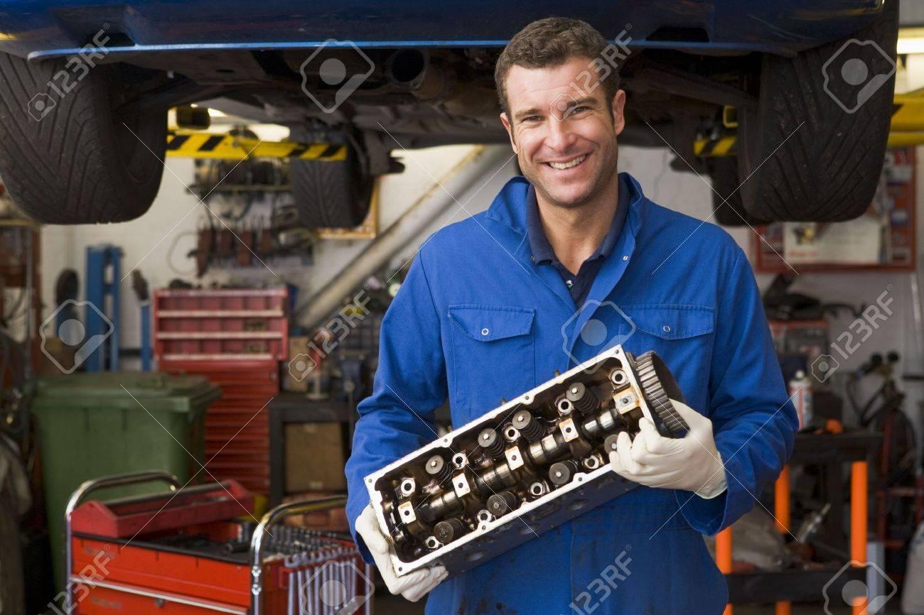 Mechanic holding car part smiling Stock Photo - 3603631