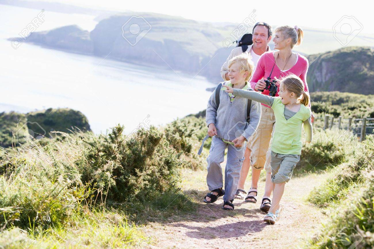Family walking on cliffside path pointing and smiling Stock Photo - 3726349