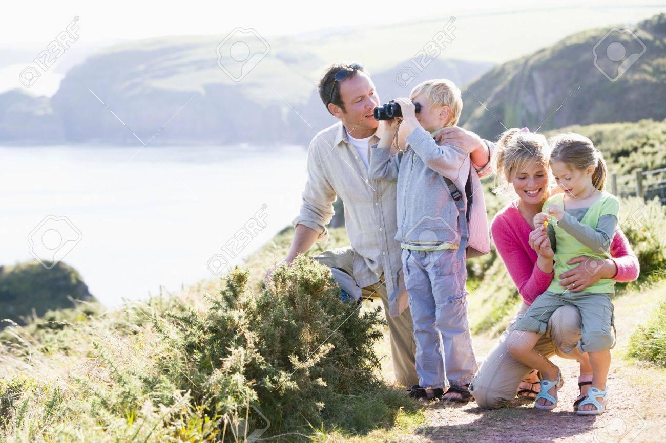 Family on cliffside path using binoculars and smiling Standard-Bild - 3603447