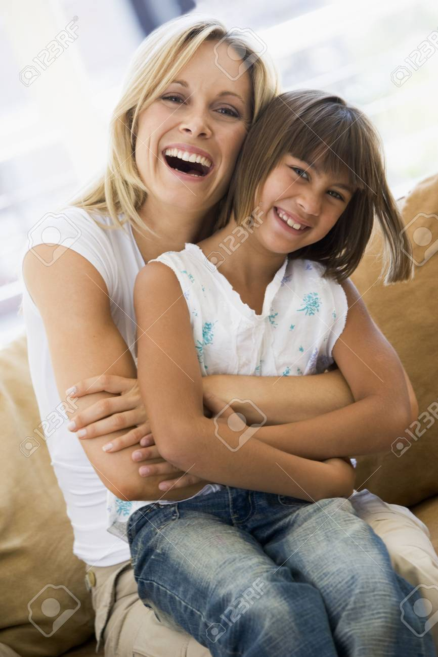 Woman and young girl sitting in living room smiling Stock Photo - 3601477