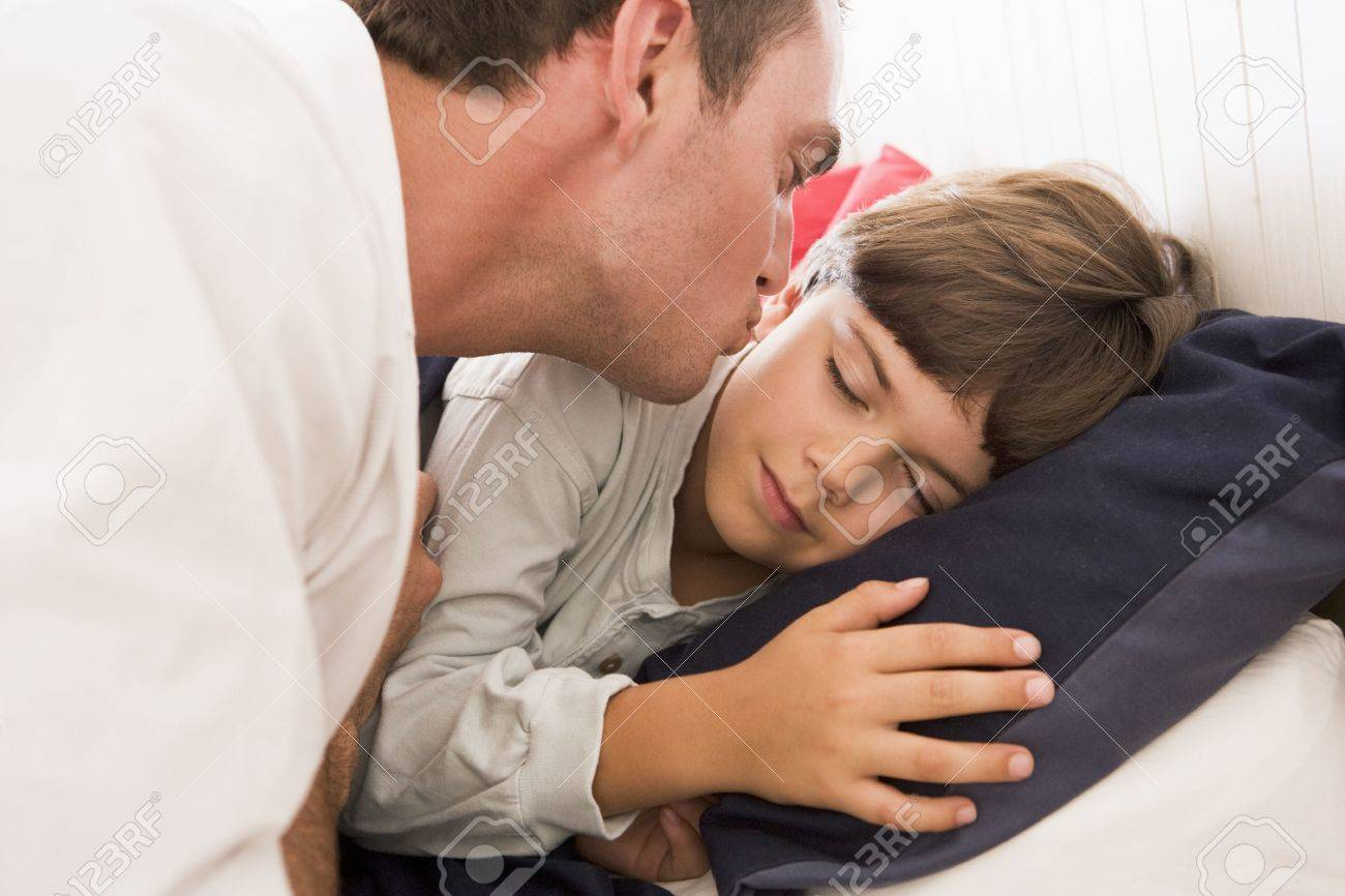 Man waking young boy in bed with kiss Stock Photo - 3602715