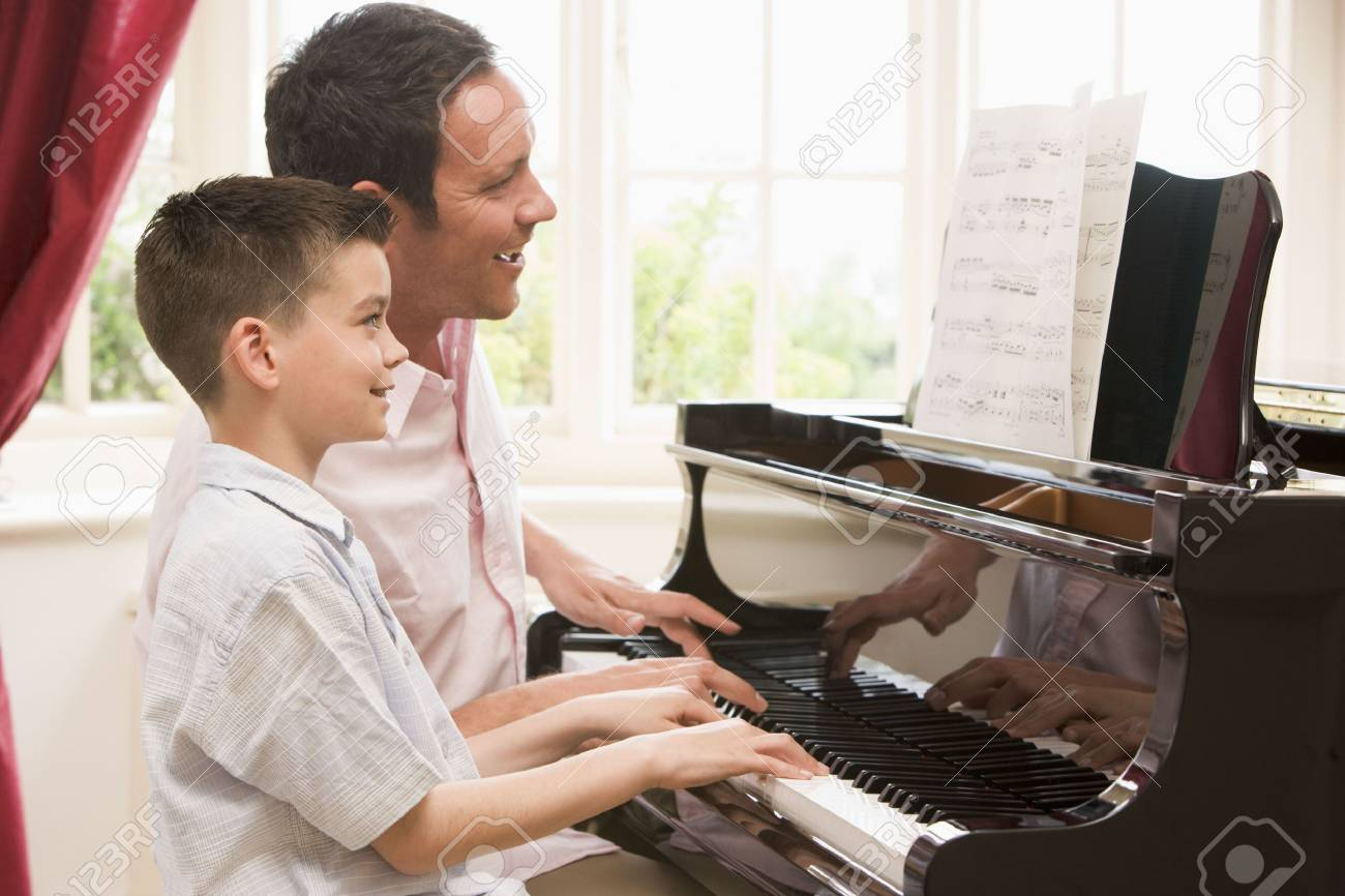 Man and young boy playing piano and smiling - 3601355