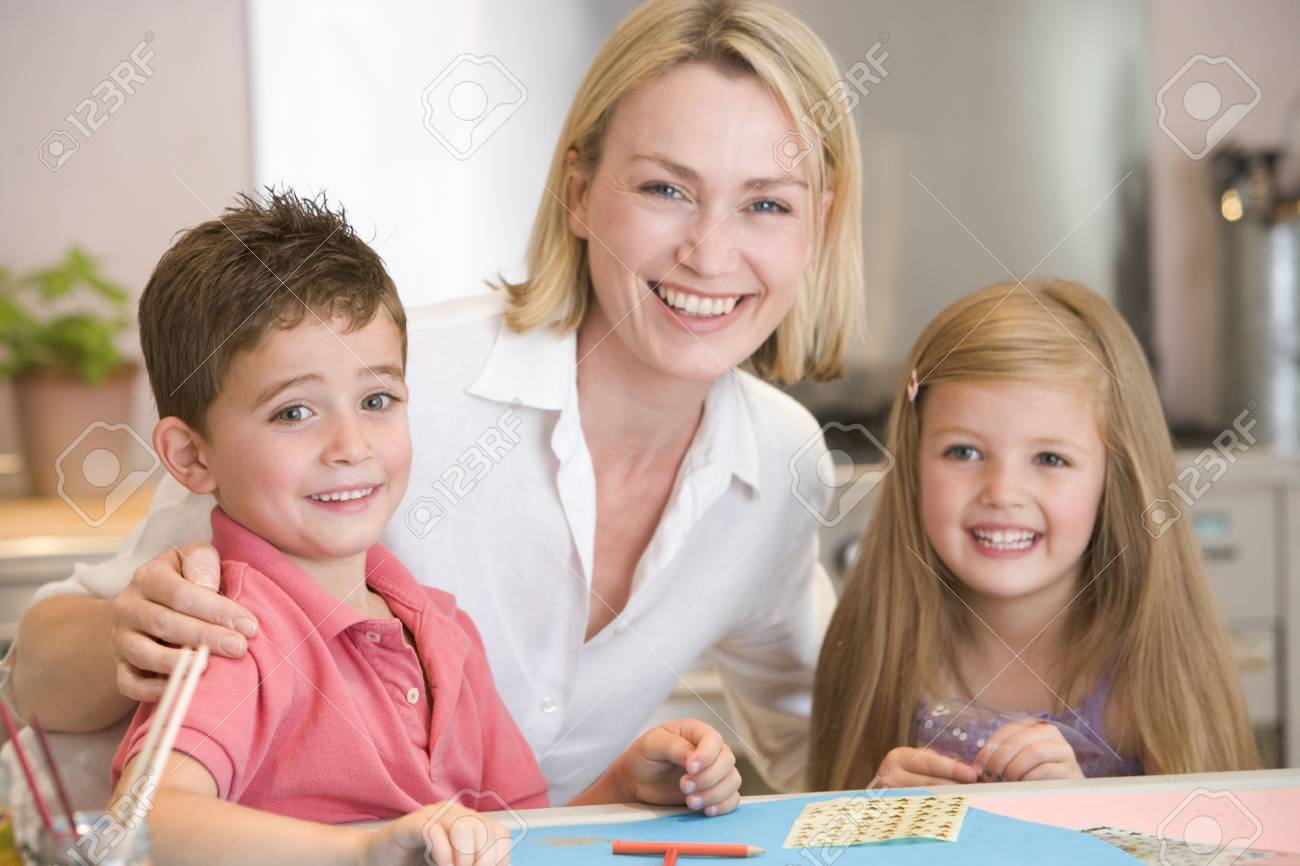 Woman and two young children in kitchen with art project smiling Stock Photo - 3601329