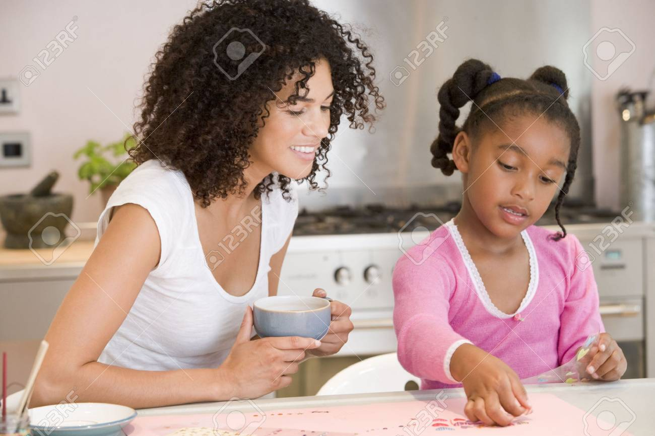 Woman and young girl in kitchen with art project smiling Stock Photo - 3602699