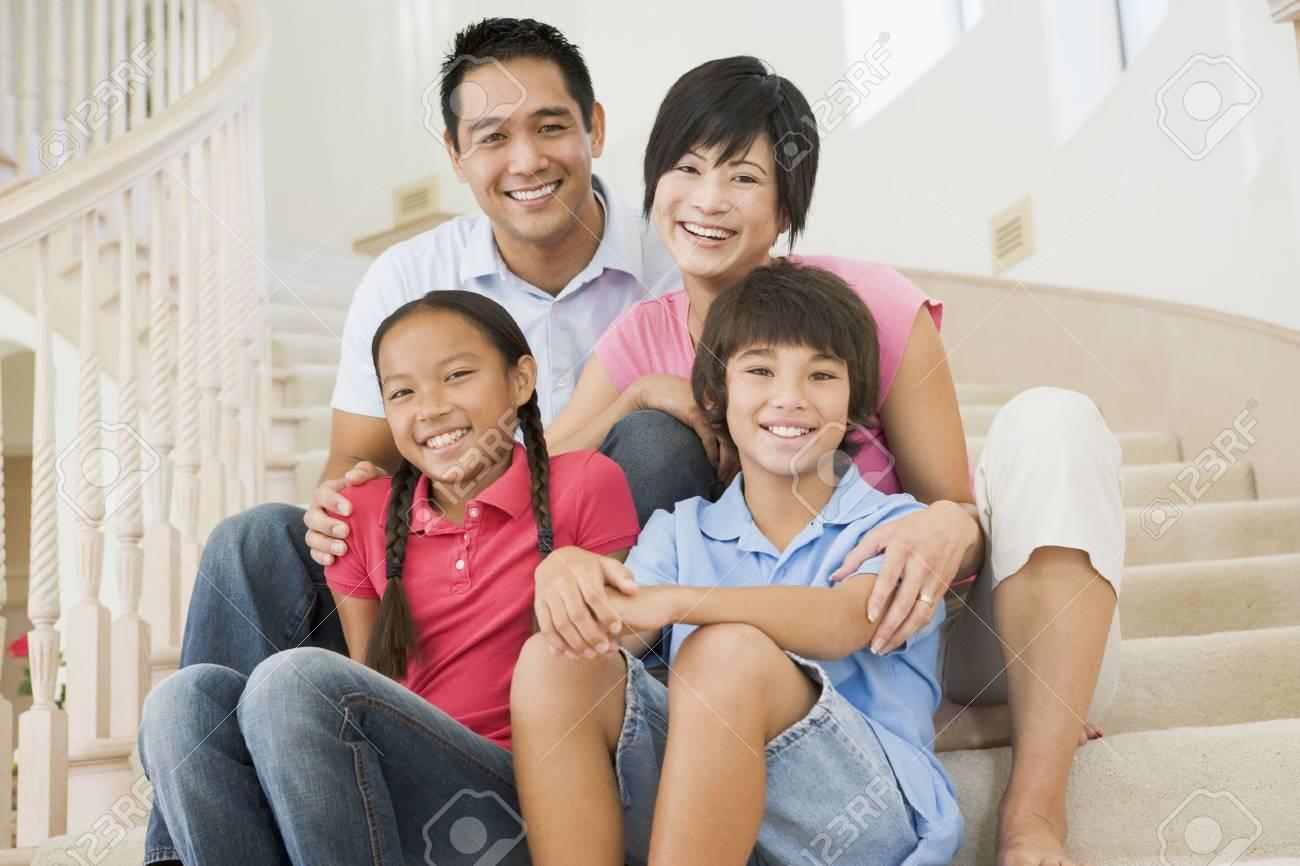 Family sitting on staircase smiling Stock Photo - 3602716