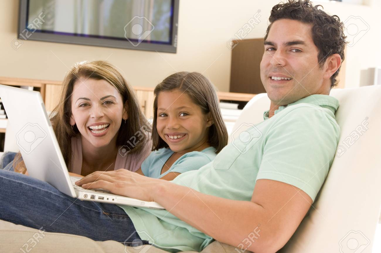 Family in living room with laptop smiling Stock Photo - 3601415