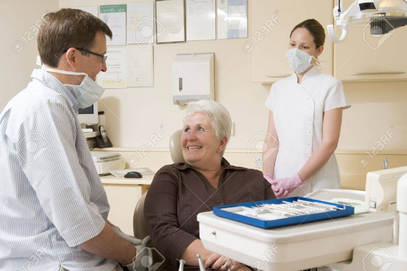 Dentist and assistant in exam room with woman in chair smiling Stock Photo - 3600834