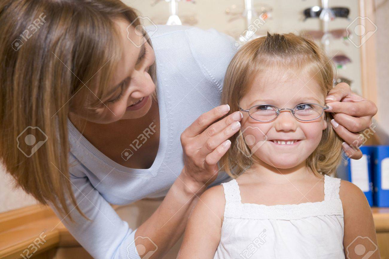 Woman trying eyeglasses on young girl at optometrists smiling Stock Photo - 3485741