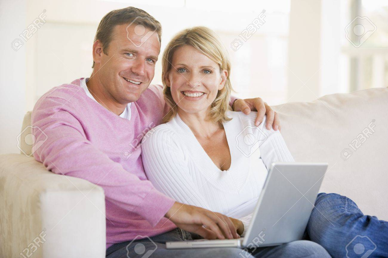 Couple in living room using laptop and smiling Stock Photo - 3484675
