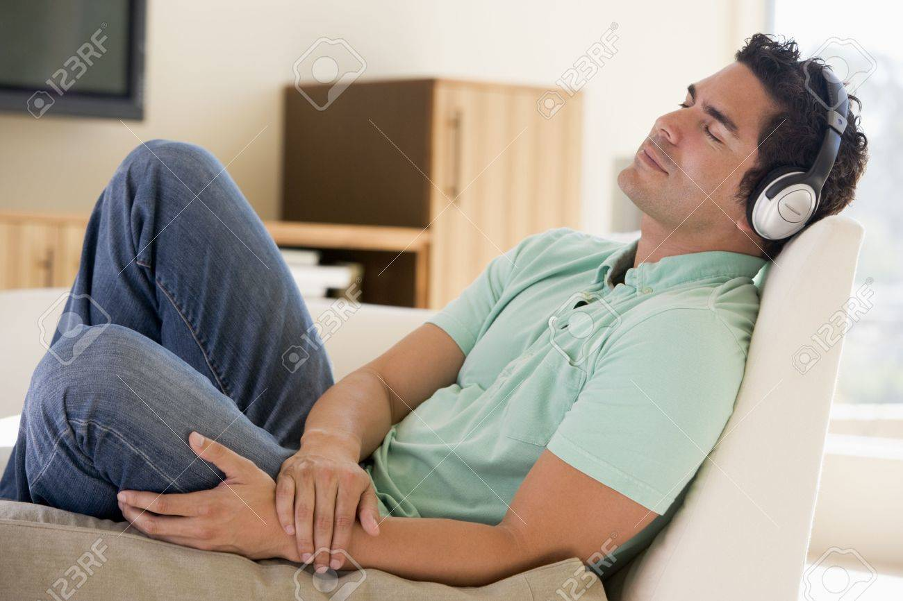 Man in living room listening to headphones sleeping Stock Photo - 3485478